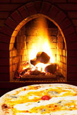 Pizza quatro formaggi and open fire in stove — Stock Photo