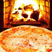 Pizza margherita and open fire in stove — Stock Photo