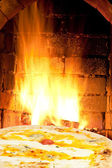 Pizza quatro formaggi and fire flames in oven — Stock Photo
