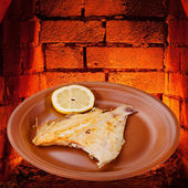 Fried sole fish on plate and hot bricks of oven — Foto de Stock