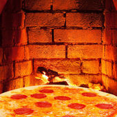 Pizza with salami and hot brick wall of oven — Foto de Stock