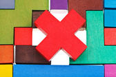 Cross shaped block on wooden puzzle — Stock Photo