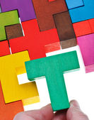 Placing T-shaped piece in wooden puzzle — Stock Photo