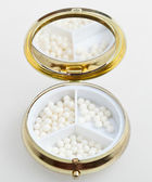 Pill box with sugar homeopathy balls — Stock Photo