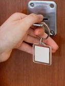 Closing house door by key with blank keychain — Stock Photo
