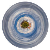 Planet with forest and hoses in grey autumn clouds — Stock Photo