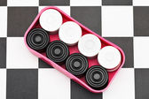 Box with checkers on checkerboard — Stock Photo