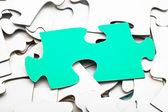 One green piece on pile of white jigsaw puzzles — Zdjęcie stockowe