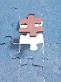 Setting the brown last piece of puzzle — Stock Photo