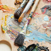 Few paintbrushes on used artistic pallette — Stock Photo