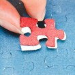 Assembling the last red piece of puzzle — Stock Photo #44721419