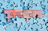 Few connected pieces on pile of separated puzzles — Stock Photo