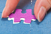 Inserting the last pink piece of puzzle — Stock Photo