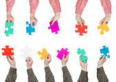 Male hands in shirt sleeves with puzzle pieces — Stock Photo
