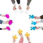 Sides with people hands holding puzzle pieces — Stock Photo