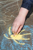 Girl paints sun in blue sky with chalks outdoors — Stock Photo