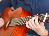 Woman plays on classical acoustic guitar — Stock Photo