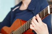 Girl plays on modern acoustic guitar — Stock Photo