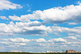 Cityscape with white fluffy clouds in blue sky — Stock Photo
