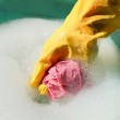 Hand in yellow rubber glove rinsing wet duster — Stock Photo #46899947