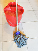 Red bucket with foamy water and mopping the floor — Stock Photo