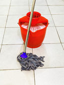 Red bucket with foamy water and mop the floor — Stock Photo