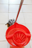 Red bucket with water and mopping the floor — Photo