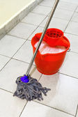 Red bucket with washing water and mop the floor — Stock Photo
