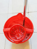 Mop in red bucket with washing water — Stok fotoğraf