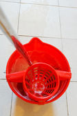 Mop in red bucket with foamy water — Stock Photo