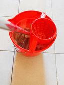 Swab in red bucket with foamy water — Stok fotoğraf