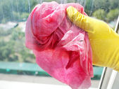 Hand in yellow glove cleaning window glass — Stock Photo