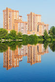Brick apartment houses along city pond — Stock Photo