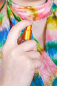 Girl spraying perfume on silk scarf from atomizer — Stock Photo