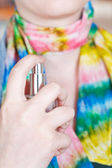 Woman sprays perfume on silk scarf from atomizer — Stock Photo