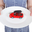Woman holds white plate with red car i — Stock Photo #48390897