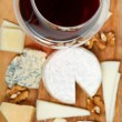 Red wine glass and portion of sliced cheeses — Stock Photo