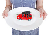 Woman holds white plate with red car i — Stock Photo