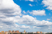 Many woolpack clouds over city in summer — Stock Photo