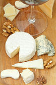 Red wine glass and sliced cheeses — Foto Stock