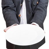 Front view of businessman holds empty white plate — Stock Photo
