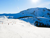 Ski run on snow slopes of mountains in sunny day — Stock Photo