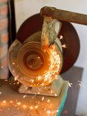 Sharpening garden hoer using a grinding machine — Stock Photo