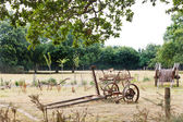 Peasant household with abandoned farm equipment — Stock Photo