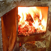 Burning wood in furnace with open door — 图库照片