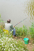 Fisherman catches a fish from riverbank — Stock Photo