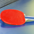Red bat, tennis ball on blue ping pong table — Stock Photo #51651953