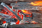 Flame over burning wood-burning coals — Stock Photo
