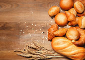 Assortment of baked bread on wood table — Stock Photo