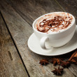Coffee cup and beans, cinnamon sticks, nuts and chocolate on woo - Stockfoto